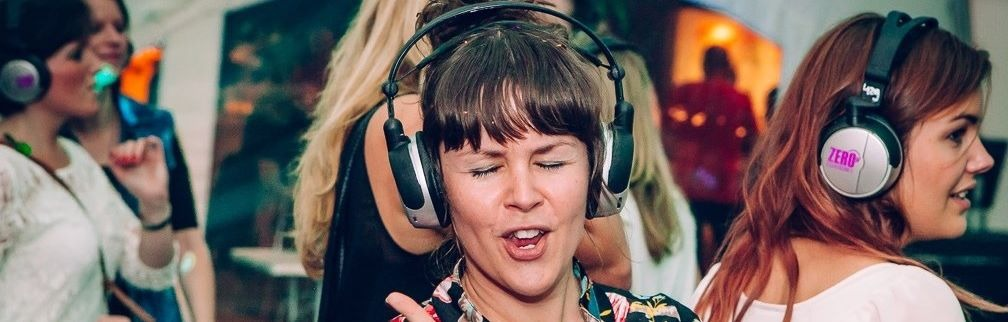 Smiling women dancing with headphones in silent disco on corporate event