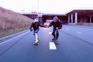 Two skateboarders towed on highway behind car of brand Opel Adam in Amsterdam